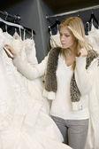Młoda kobieta, patrząc na tag cena sukni ślubnej w butiku — Zdjęcie stockowe