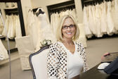 Portrait of a happy senior woman wearing eyeglasses sitting in bridal store — Stock Photo