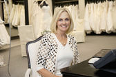 Portrait of a happy senior woman sitting in bridal store — Stock Photo