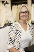 Portrait of a happy senior woman wearing eyeglasses sitting in bridal boutique — Stock Photo