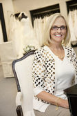 Portrait of a happy senior female wearing eyeglasses sitting in bridal boutique — Stock Photo
