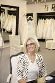 Portrait of a happy senior female wearing eyeglasses sitting in bridal store — Stock Photo
