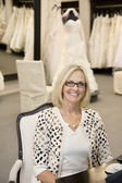 Portrait of a happy woman sitting on chair in bridal store — Stock Photo