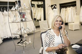 Portrait of a happy woman making a call in bridal store — Stock Photo