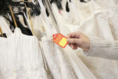 Cropped shot of female hands holding price tag attached to wedding gown in bridal boutique — Stock Photo