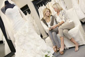 Tilt shot of mother and daughter sitting with footwear in bridal store — Stok fotoğraf