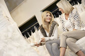 Happy mother and daughter sitting footwear in bridal store — Stock Photo