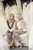 Happy mother and daughter looking at each other while sitting on sofa in bridal boutique — Stock Photo