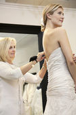 Beautiful woman dressed up in wedding dress while senior owner helping in bridal store — Stock Photo