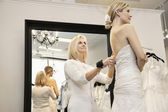 Senior owner assisting young bride getting dressed in wedding gown — Stock Photo