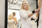 Happy senior owner with pincushion in wrist helping bride getting dressed — Stock Photo