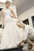 Senior employee adjusting wedding dress of beautiful young bride in bridal store — Stock Photo