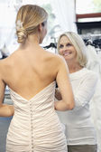 Back view of woman dressed in bridal gown with happy senior owner assisting — Stock Photo
