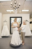 Beautiful woman dressed up as bride with senior employee helping in bridal store — Stock Photo