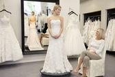 Glückliche mutter auf der suche nach jungen tochter gekleidet in brautkleid in hochzeits-boutique — Stockfoto