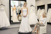 Happy mother looking at young daughter dressed in wedding gown in bridal boutique — Stok fotoğraf