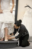 Mature female employee helping bride with footwear in bridal boutique — Stock Photo