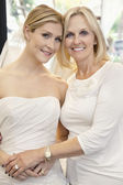 Portrait of a mother with daughter dressed as bride in bridal store — Stock Photo