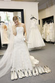 Beautiful young woman confused while selecting footwear in bridal boutique — Stock Photo