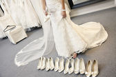 Low section of young woman standing with variety of footwear in bridal boutique — Stock Photo