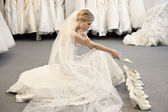 Side view of young woman in wedding dress confused while selecting footwear — Stock Photo