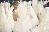 Achteraanzicht van een jonge vrouw in trouwjurk, bruids toga's kijken tentoongesteld in boetiek — Stockfoto