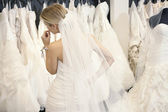 Back view of a young woman in wedding dress looking at bridal gowns on display in boutique — Stok fotoğraf