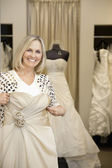 Portrait of a happy senior woman holding wedding gown in bridal store — Stock Photo