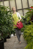 Young woman with watering can in greenhouse — Stock Photo