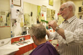 Barber cutting senior man's hair in barbershop — Stock Photo