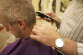 Midsection of senior barber giving haircut to customer in salon — Stock Photo