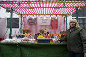 Portrait of a happy senior fruit stall owner standing in market — Stock Photo