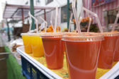 Close-up of fruit juices on display at market stall — Foto Stock