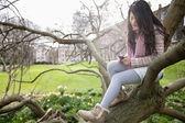Młoda kobieta siedzi na gałęzi drzewa podczas wiadomości tekstowych — Zdjęcie stockowe