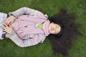 Top view of young Asian woman with long black hair lying on lawn — Stock Photo