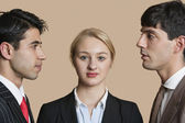 Portrait of a young businesswoman with male colleagues staring at each other over colored background — Stock Photo