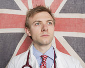 Caucasian doctor looking away with British Flag in background — Stock Photo