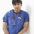 Portrait of an Indian male doctor leaning over white background — Stock Photo #21890411