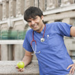 Portrait of an Indian male doctor holding a green apple — Stock Photo #21890419
