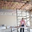 Stock Photo: Portrait of happy female contractor with building plans