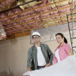 Team of architects looking away with blueprints at construction site — Stock Photo