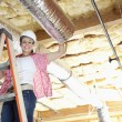 Portrait of a happy woman standing on ladder working on unfinished ceiling — Stock Photo
