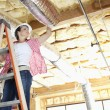 Low angle view of female worker working on incomplete ceiling — Foto Stock