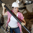 Portrait of young construction worker holding pipe - Stock Photo