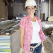 Portrait of a happy young woman architect wearing hardhat at construction site — Stock Photo #21890801