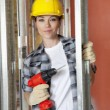 Portrait of beautiful mid adult contractor with drill — Stockfoto