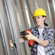 Stock Photo: Mid adult worker drilling at construction site