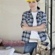 Portrait of female worker standing with arms crossed at construction site — Stock Photo