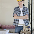 Portrait of female worker standing with arms crossed at construction site — Stock Photo #21890989