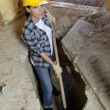 Portrait of female worker digging with shovel at construction site — 图库照片